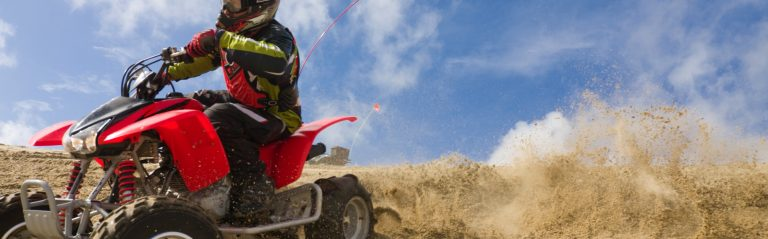 A person riding an ATV through a sand pit at perilously high speed.
